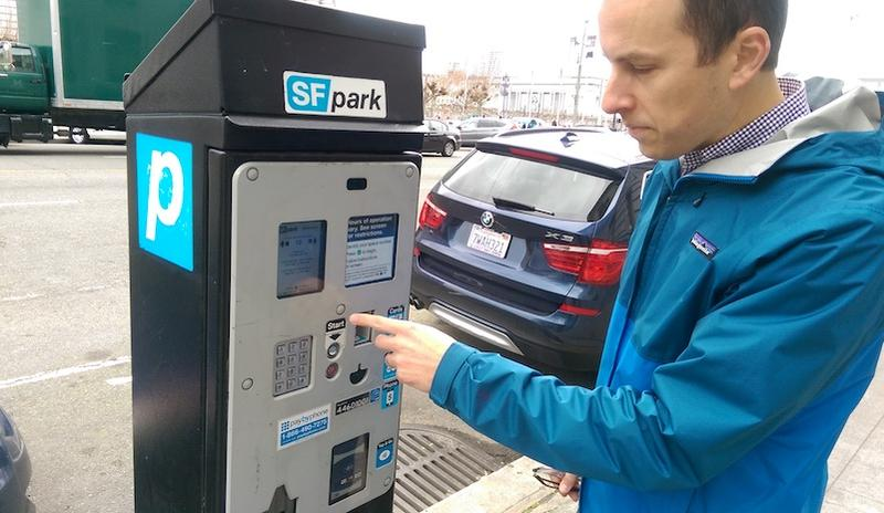 Hank Willson, San Francisco's Parking Policy Manager, operates a parking meter by City Hall