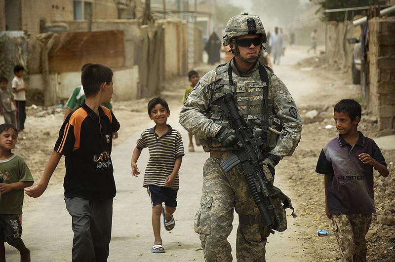 Iraqi children gather around as U.S. Army Pfc. Shane Bordonado patrols the streets of Al Asiriyah, Iraq, on Aug. 4, 2008