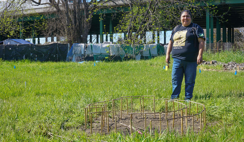 Corrina Gould stands on land recently acquired by the Sogorea Te' Land Trust. In front of her is a model of the traditional arbor they will be building on site. The Shuumi Land Tax has allowed Gould to organize around indigenous land full time.