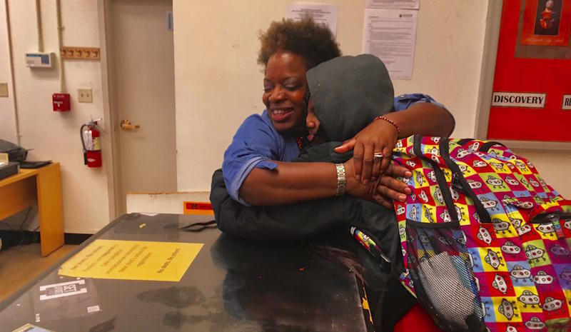Destiny Shabazz, 17, gets a hug from a front office administrator at West Oakland's McClymonds High School.  Destiny has no parent or legal guardian. She's not in foster care, and she's not emancipated