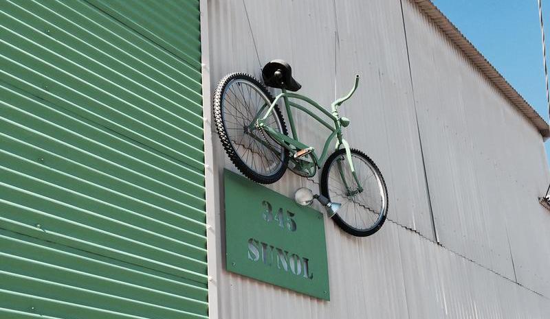 A bike hangs on the wall outside Good Karma Bikes in San Jose