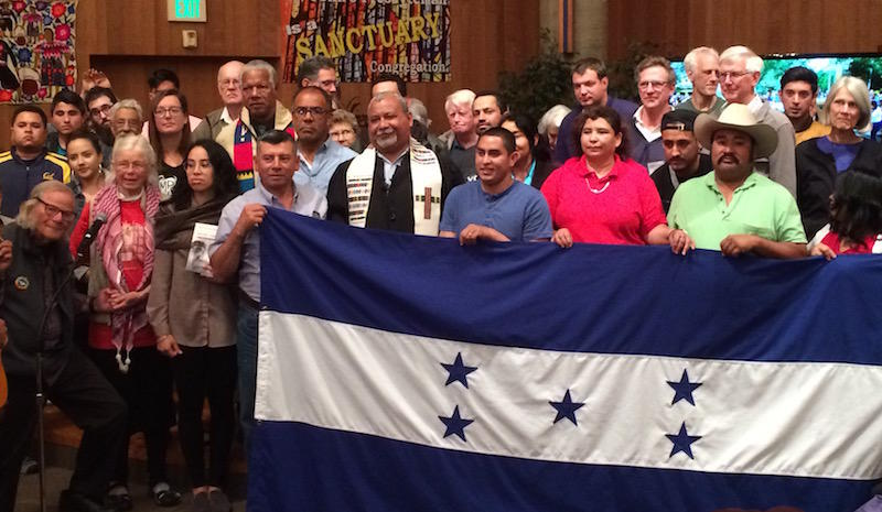 Padre Melo behind the Honduran flag and surrounded by supporters at St. John's Presbyterian Church in Berkeley