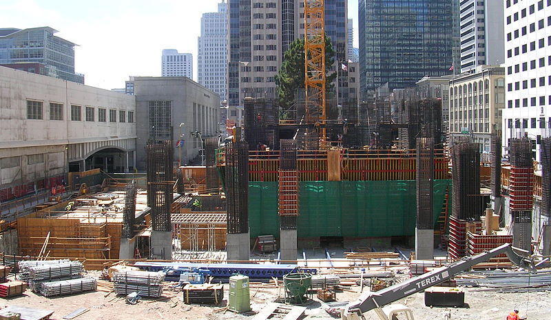 The Millennium Tower (301 Mission Street) under construction, showing the crane footing, concrete core and construction equipment. The Transbay Terminal is visible to the left.