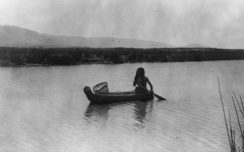 A Pomo man paddles a canoe on Clear Lake, 1924.
