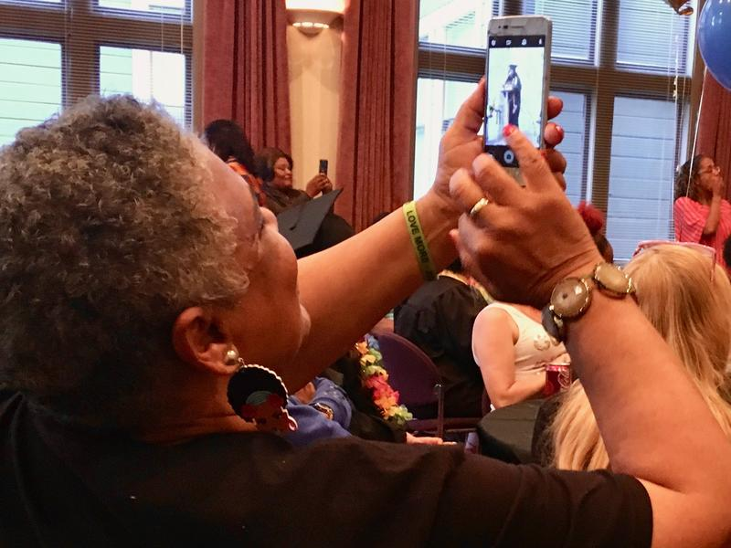 Florida's grandmother takes a photo at the EMERGE graduation as the 16-year-old stands to receive her high school diploma.