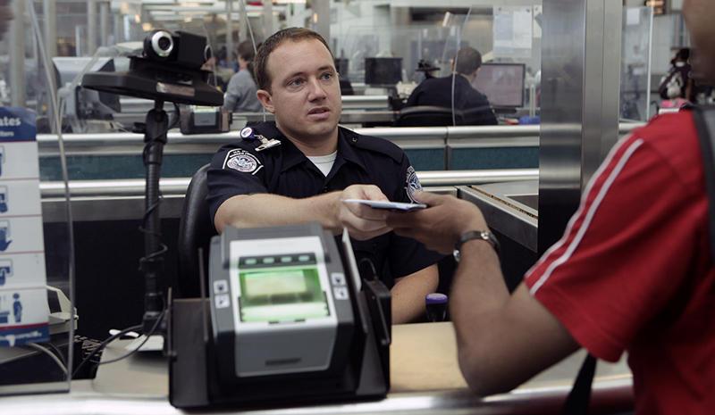 A CBP Officer processes an incoming passenger at the Newark International Airport
