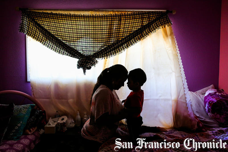 Jorgito, 5, and his cousin and caretaker Margarita (left) share a moment together in their bedroom after taking a portrait in San Mateo, California, on Thursday, July 5, 2018.