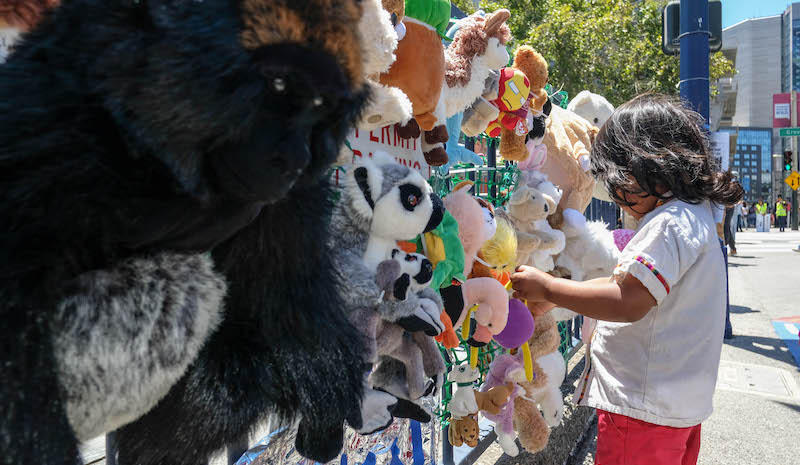 A child investigates a display of stuffed animals - each one represents a migrant child held in detention.