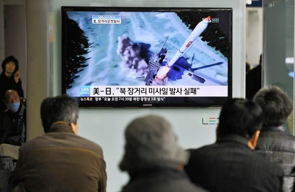 South Koreans at a train station in Seoul watch a TV graphic of North Korea's rocket launch.