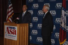 Former presidential nominee Mitt Romney speaks to reporters as he endorses Asa Hutchinson.