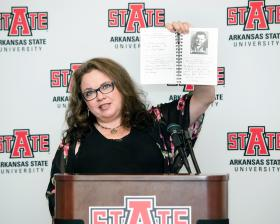 Tara Cash Schwoebel, Johnny Cash's youngest daughter, shows one of the many photos in the book.  Photo courtesy of Arkansas State University.