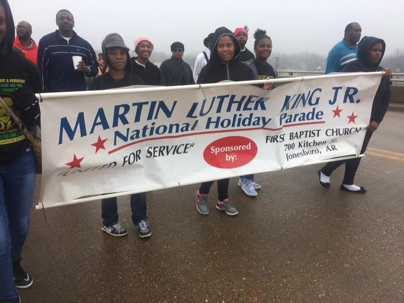 Participants of the 2017 Craighead County Dr. Martin Luther King Jr. Day parade walking across the Jonesboro Main St. bridge.