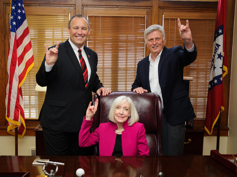 "Kays House Preview— (from left) Arkansas State University Chancellor Kelly Damphousse, former Arkansas first lady Ginger Beebe and former Arkansas Governor Mike Beebe give a ""Wolves Up"" sign in the re-created governor's office at the restored Kays House."
