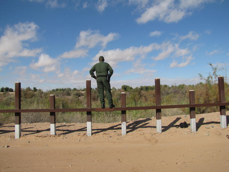 Bryon Strom, Yuma Sector U.S. Border Patrol agent, stands on the post-on-rail border fence near Yuma, Arizona, looking into Mexico across the Colorado River