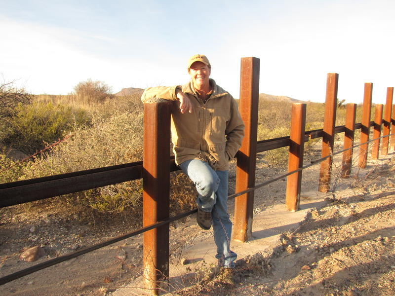 Kelly Glenn-Kimbro leans against the post-on-rail border barrier separating Douglas, AZ and Sonora, Mexico