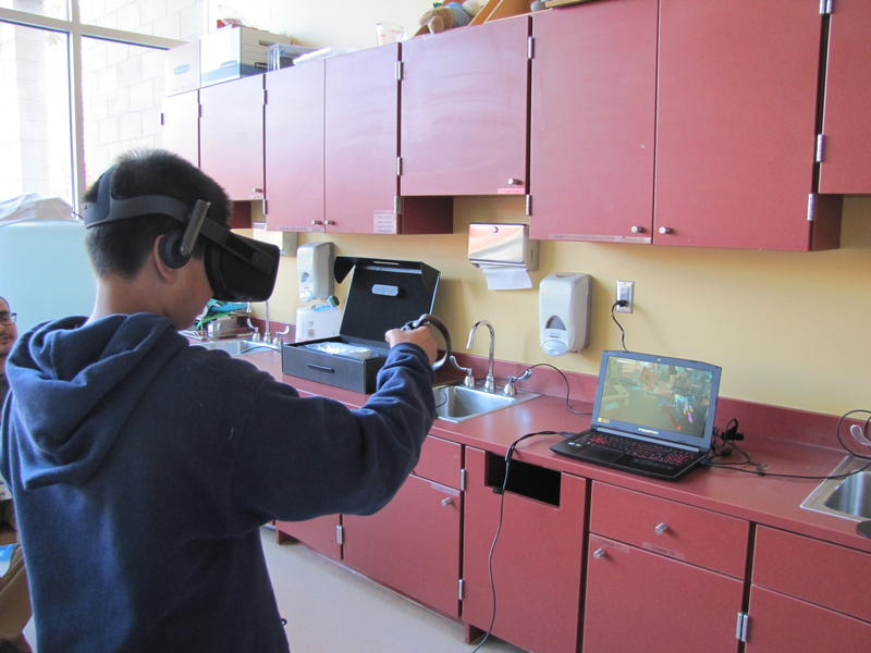 A teenage library patron checks out the virtual reality system at the Yuma Main Library