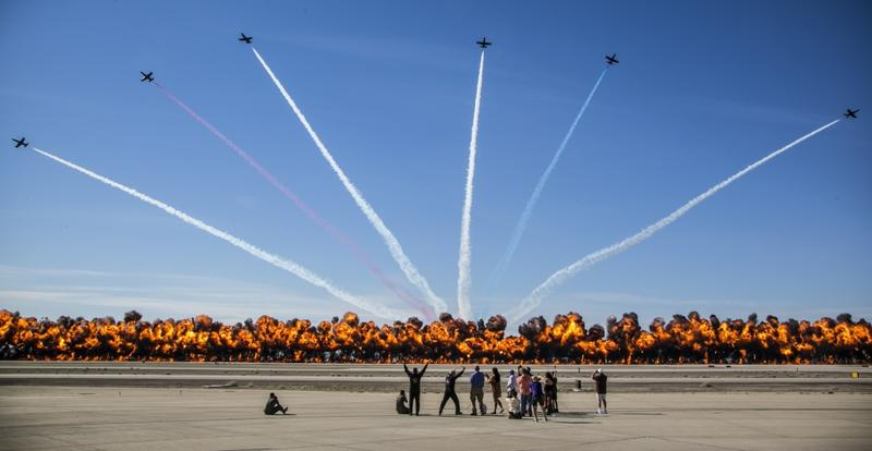 "The Patriots Jet Team performs aerial acrobatics as pyrotechnics provided by the Tora Bomb Squad of the Commemorative Air Force explode, forming a ""Wall Of Fire"" during the 2017 Yuma Airshow at Marine Corps Air Station Yuma, Ariz., March 18, 2017"