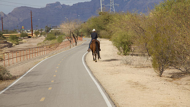 A cowboy and his horse enjoys The Loop path along the Santa Cruz River south of downtown Tucson.