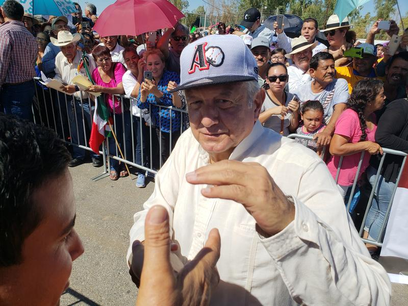 Mexican President-Elect Andres Manuel Lopez Obrador greets supporters as he wears a hat from the Algodoneros (Cottonmen) baseball team in San Luis Rio Colorado on Friday, September 21, 2018.