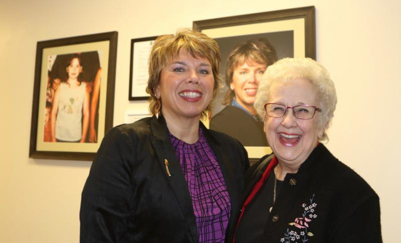 Minnesota Supreme Court Justice Anne McKeig sharing a laugh with Dee Hillstrom who was one of her instructors at Northland High School in Remer. The two are standing in front of photos of Justice McKeig that hang in the Cass County Court House in Walker