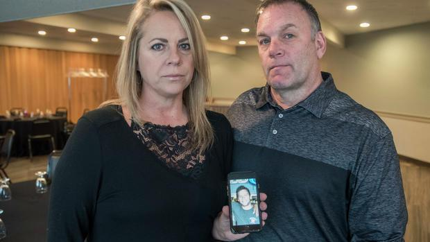Rep. Dave Baker and his wife Mary with a photo of their son lost to an opioid overdose