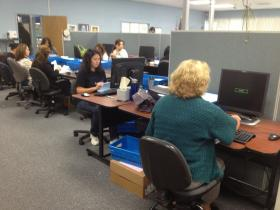 Workers in the Monterey County Elections Office prepare absentee ballots for signature verification.