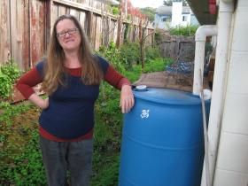 Santa Cruz Reskilling Expo Founder Bonnie Linden stands by her backyard rain catchment system.