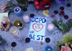 A sign placed at the memorial outside the Santa Cruz Police Department
