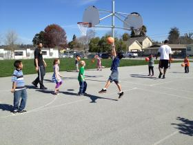 Santa Cruz Warriors basketball players Hilton Armstrong and Darington Hobson play with students from Gault Elementary.
