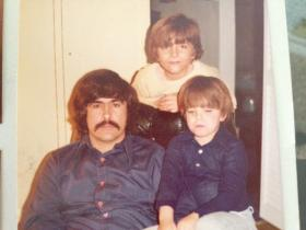 Jason, age 7, sit on the lap of his father Ronald Chelius.