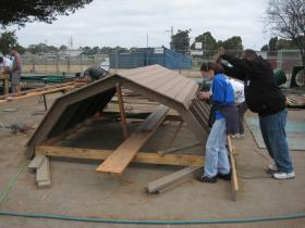Volunteers build a roof for the Tatum's Garden playground.