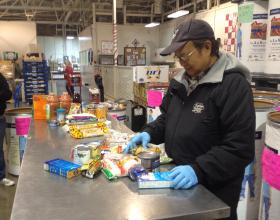 Volunteer Leonard Rang sorts through food donated during the holidays.  Volunteers must inspect each item before putting it on Food Bank shelves.