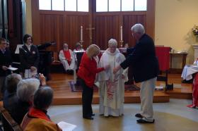 Christine Fahrenbach puts on her priest's stole for the first time.