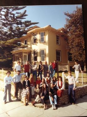 The staff of Digital Research poses outside headquarters at 801 Lighthouse Avenue in Pacific Grove in 1980.  Gary Kildall stands on the right wearing jeans and a button down shirt, his arm is up on a post.  Original photo was taken by Jerry Lebeck, Trend Photography.