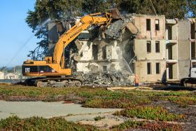 An excavator demolishes an abandoned building on the CSUMB campus.