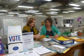 Santa Cruz County Clerk Gail Pellerin (left) leafs through the petitions to get a page count after they were handed in.