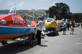 A parking lot near the Monterey Wharf acts as a staging are for boats in the Great Pacific Race.  Rower Elsa Hammond sits on her orange boat in the foreground.