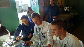 Jack Maughan (left) and Ethan Kurteff (right) with their pH sensor and the XPrize validation team.
