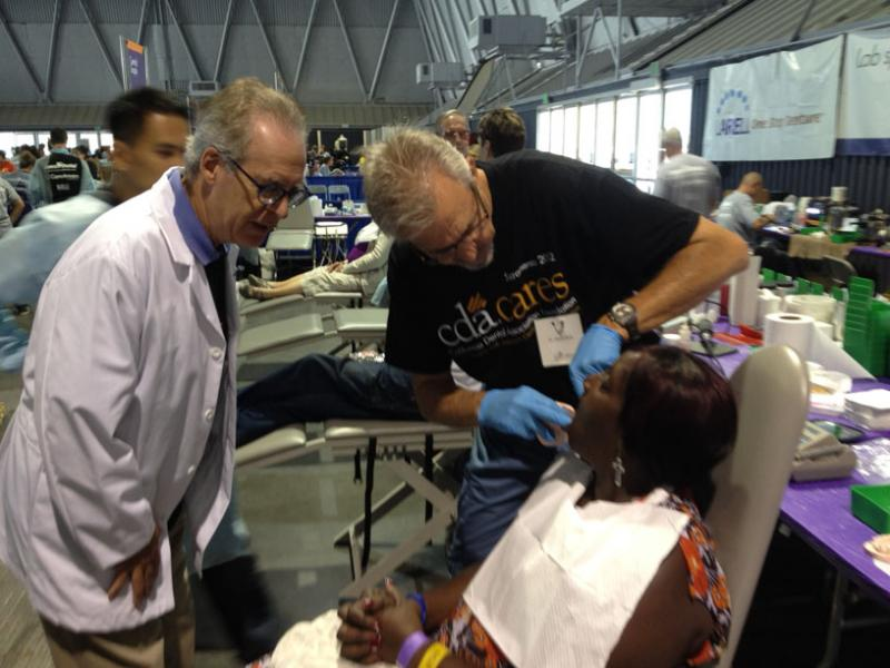 Dr. Lawrence Wallace leans in to watch Dr. Geoff Uhrik fit Yolanda Kinsey with a Larell One Step Denture.