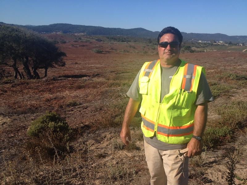 UXO Team Lead Dan Rivera stands in front of a field in the impact area that his team was clearing in late 2014.