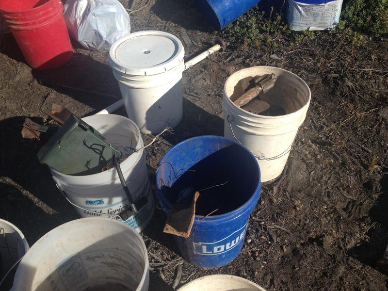 Scrap metal found in the impact area is collected in buckets.