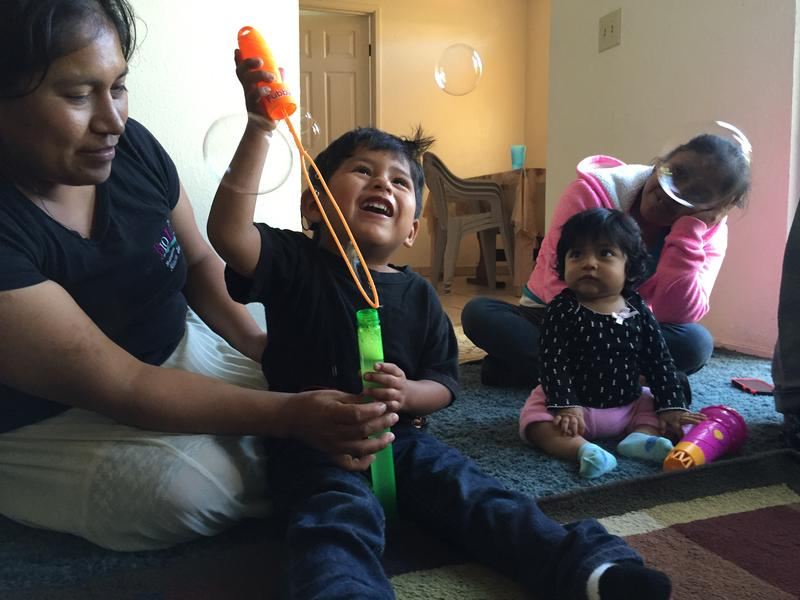 """Samuel Lopez blows bubbles while they sing """"Burbujas"""" (bubbles) during this therapy session."""