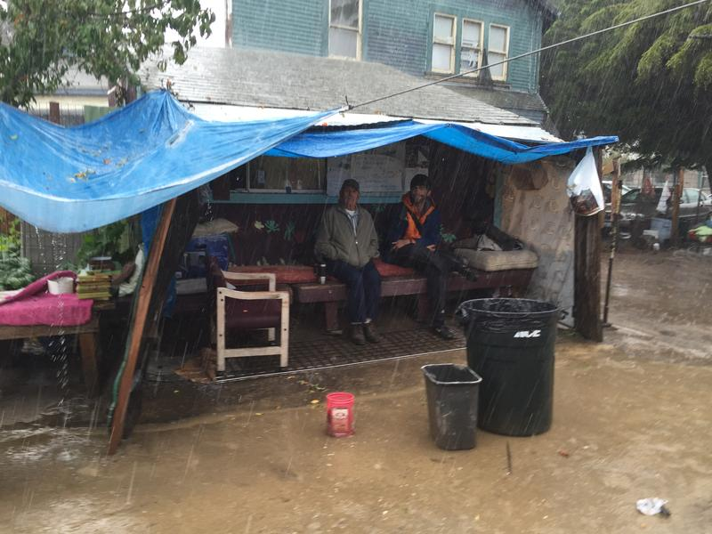 On a rainy day Emilio Martinez Castaneda and Joe Bonanno take shelter by a shed at the Beach Flats Community Garden.