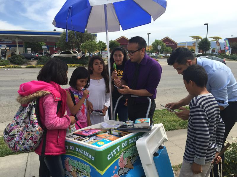 Librarian Luis Alejandre (purple shirt) and Library Clerk Luis Moya (blue shirt) help kids check out books from the Paletero cart.