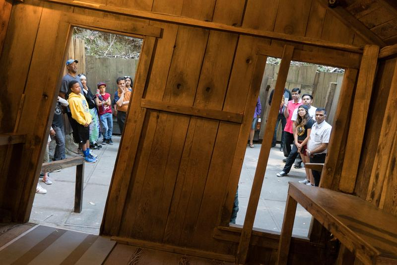 Visitors look into the the Santa Cruz Mystery Spot's crooked cabin.