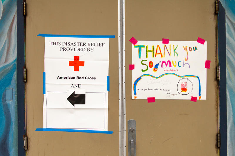 A Thank You Firefighters sign hangs on the door at the Red Cross evacuation center in Carmel.