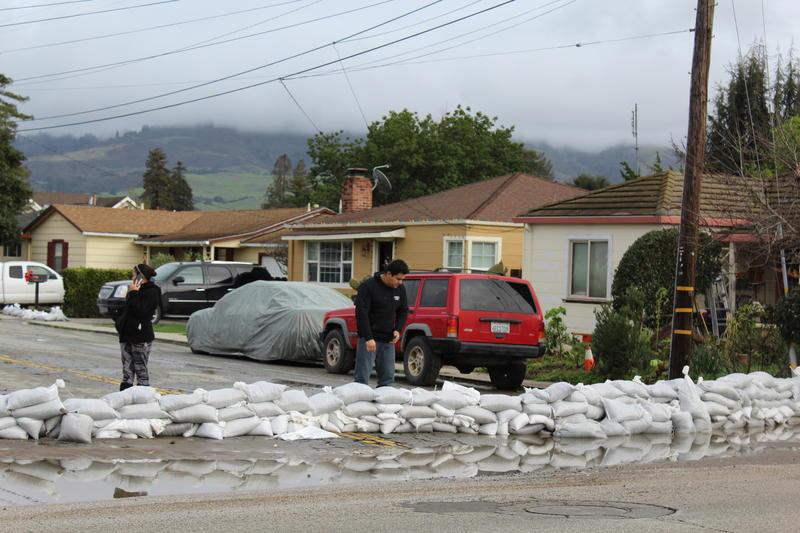 Neighbors block flood waters from entering their cul-de-sac in Interlaken with sandbags.