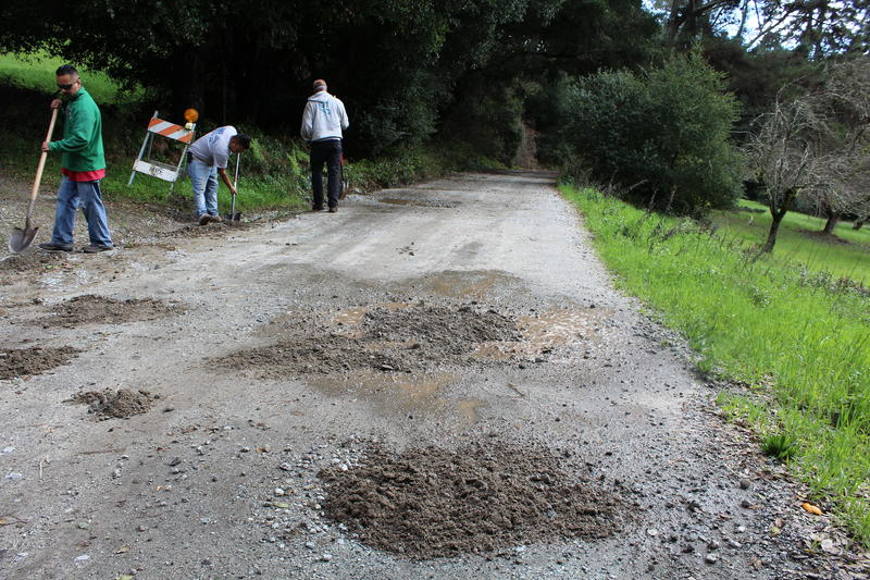 Greg Prussia and his neighbors fill in potholes on their road.