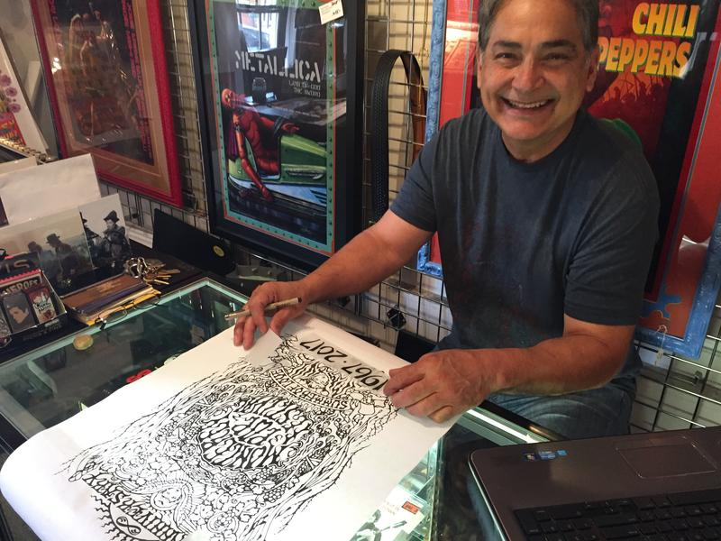 Larry Chavez works on a poster that he will sell at the Monterey International Pop Festival's this weekend.