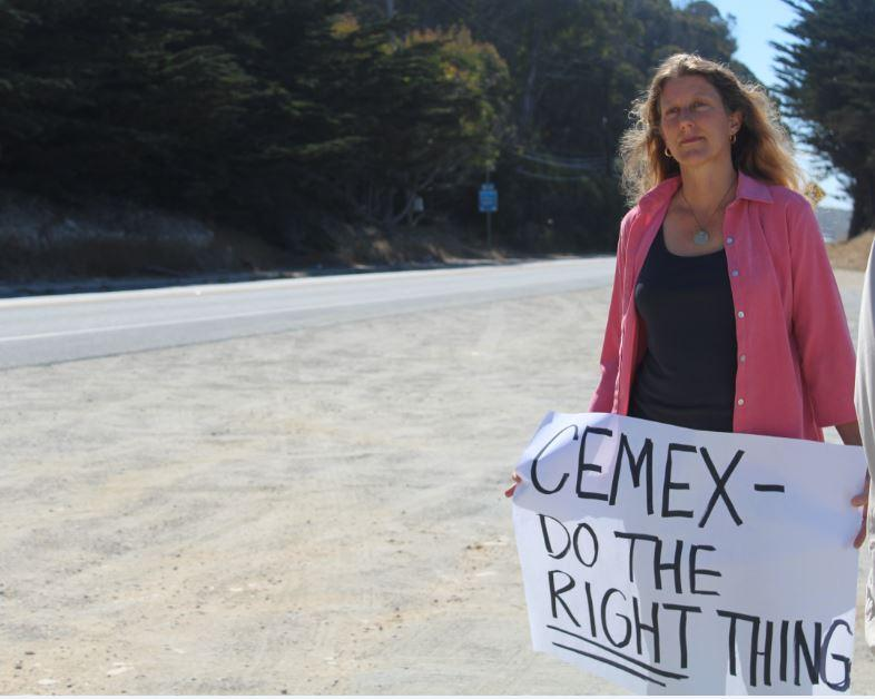 Davenport resident Jessica Wolf holds a sign urging CEMEX to repair their broken water pipeline.